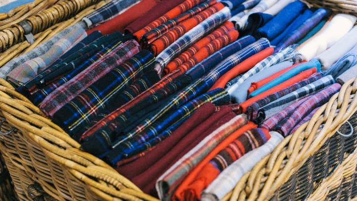 A wicker basket of folded tartan scarves