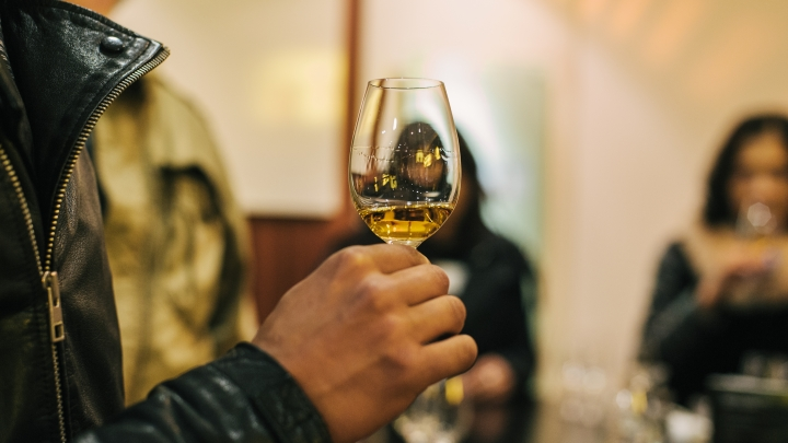 A small tulip glass with whisky in it, being held in a man's hand, as he learns how to taste whisky