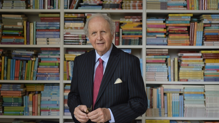 Alexander McCall Smith, wearing a dark blue jacket, light blue shirt and red tie, stands with his hands together in front of bookshelves
