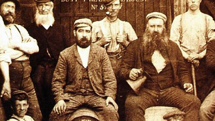 Black and white photo of Cardhu distillery team in late 19th century. Men with beards and Victorian clothes in a group, two are sitting on top of casks.