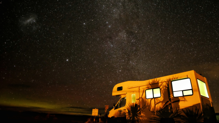 A campervan at night, with a dark, starry sky above it